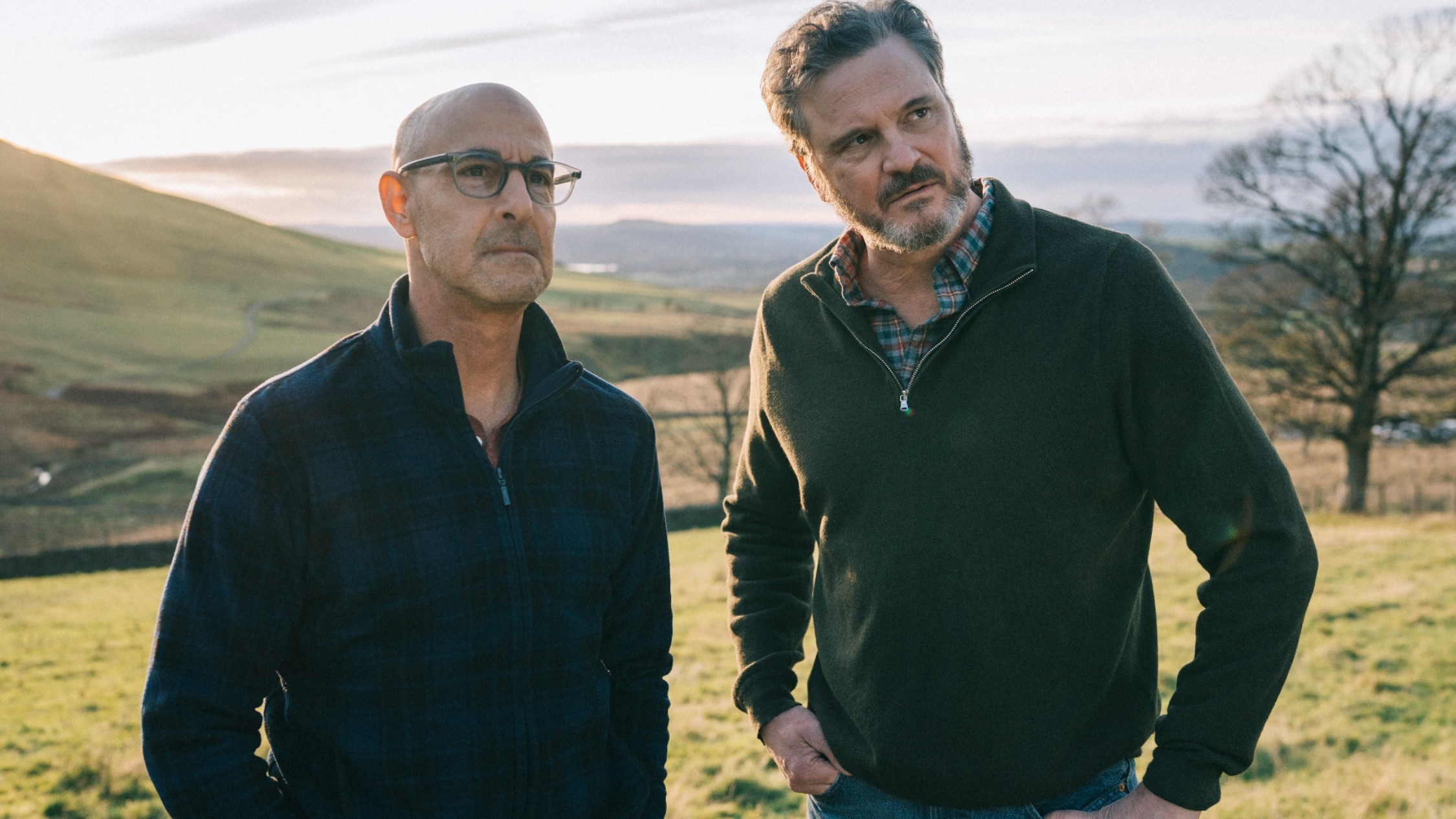 Colin Firth and Stanley Tucci in an English field with rolling hills and trees in Supernova