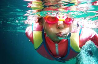 Child swimming in pool wearing goggles and vest