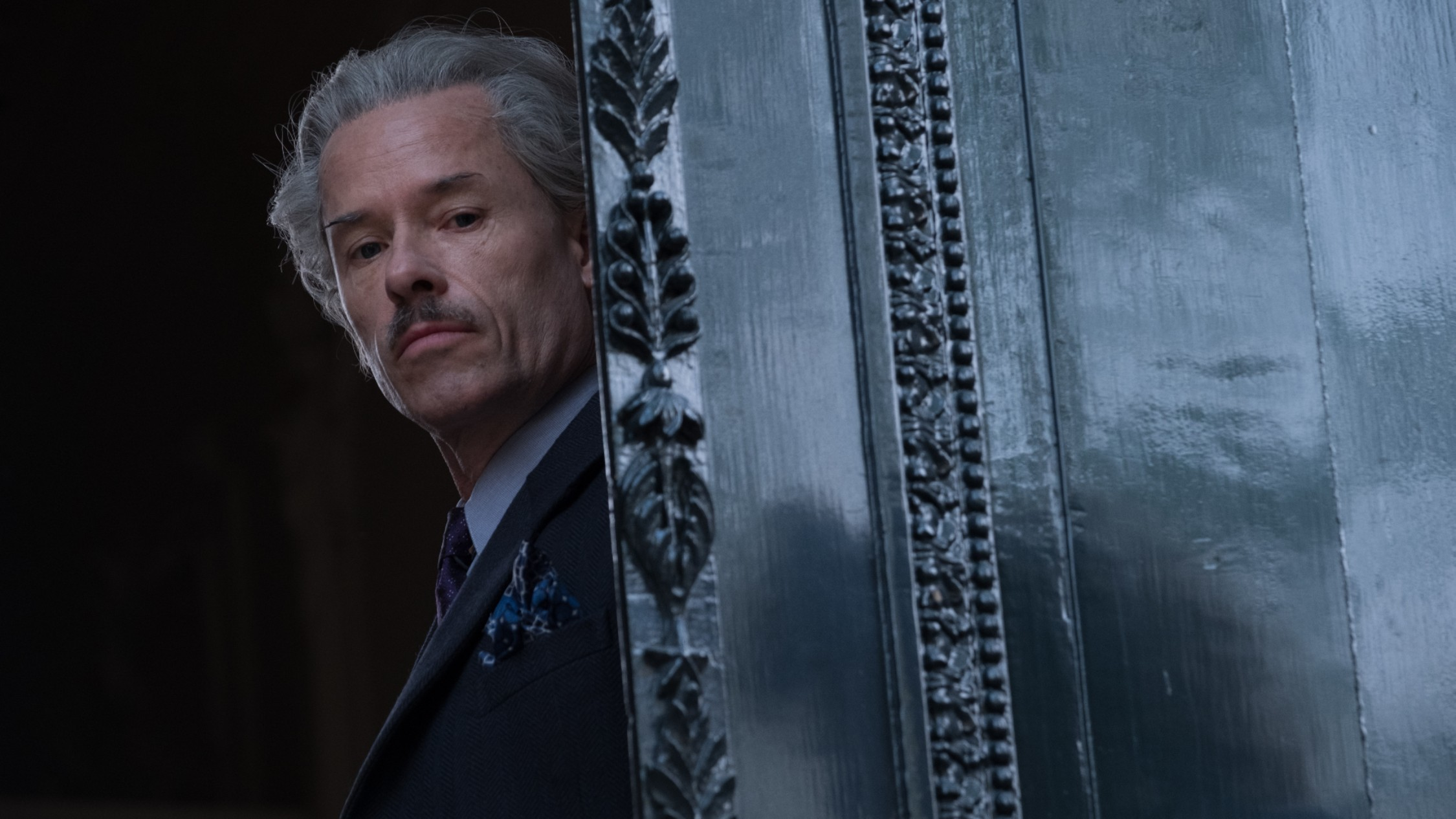 Guy Pearce with grey hair and a moustache peers out from behind an ornate door in JIFF film The Last Vermeer