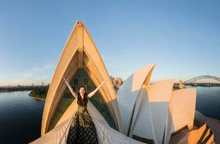 A woman in a fancy dress,  arms outsretched in front of the Opera House