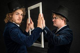 Two men in top hats and tails look through an empty picture frame toward one another