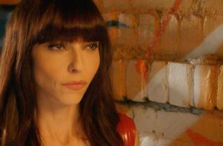 Buffy star Juliet Landau, who played Drusilla, in a shiny red sleeveless top against a bright-painted brick wall