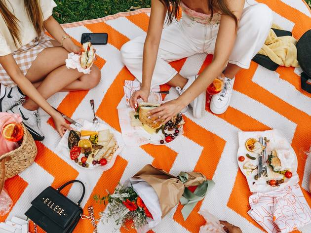 Flatlay of snacks and people sitting on a picnic rug