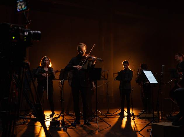 Richard Tognetti and the ACO filming their digital ACO StudioCasts with moody orange back lighting