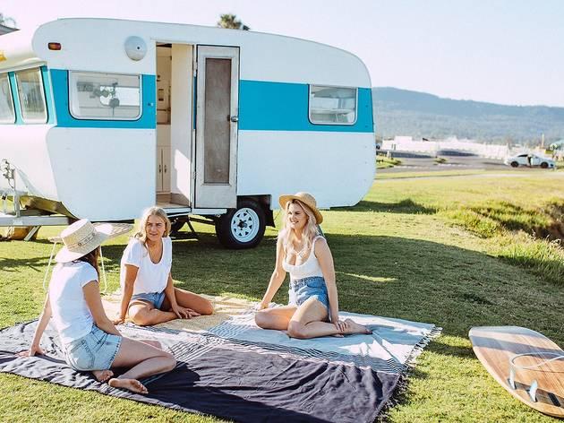Three people sit on a picnic blanket in front of a vintage caravan