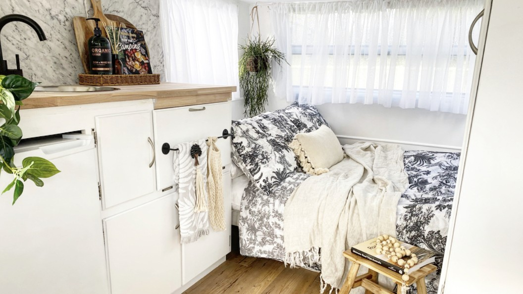 Interior of caravan with bed and white decor