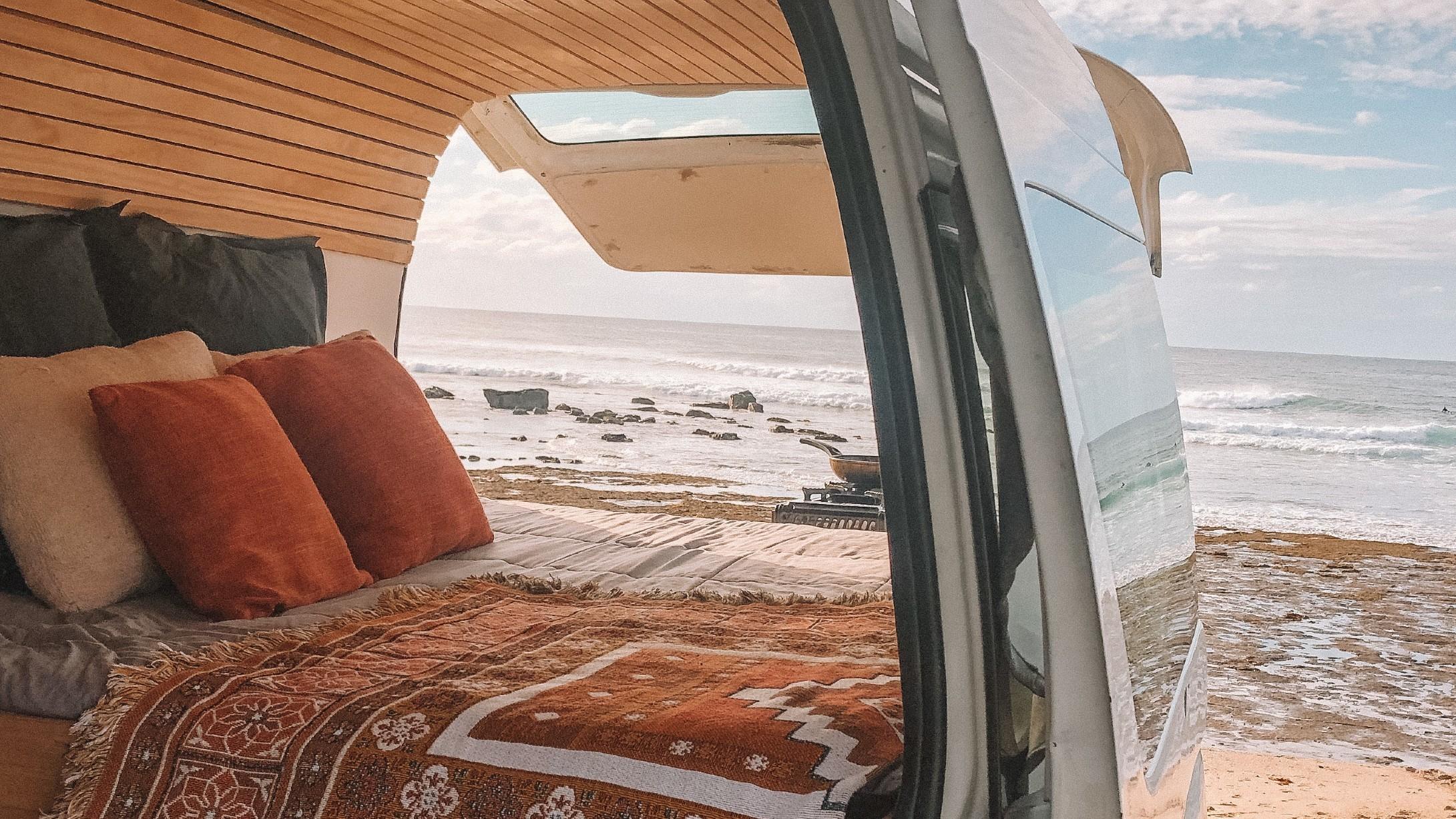 Interior of campervan with back door open to beach views