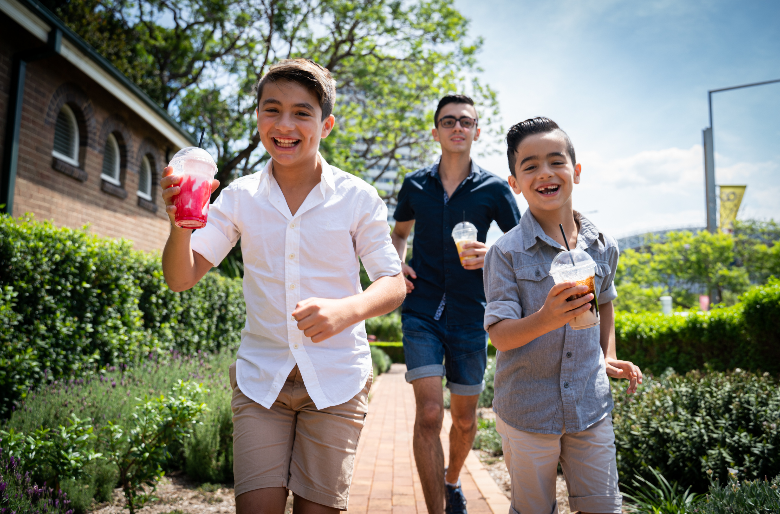 Three young people run through a garden holding colourful drinks and laughing