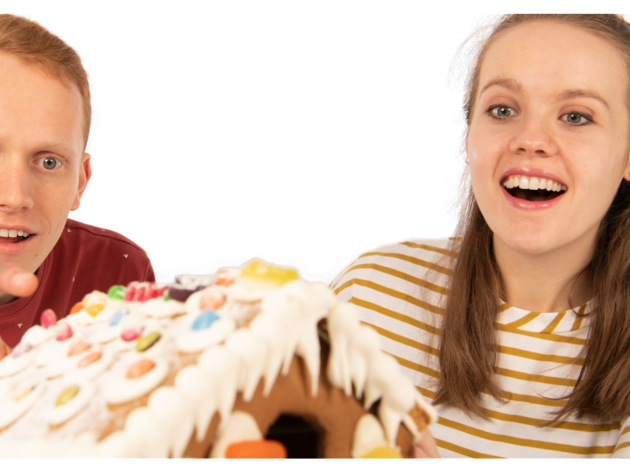 A man in a red t and a girl in a white and yellow striped one look amazed at a gingerbread house