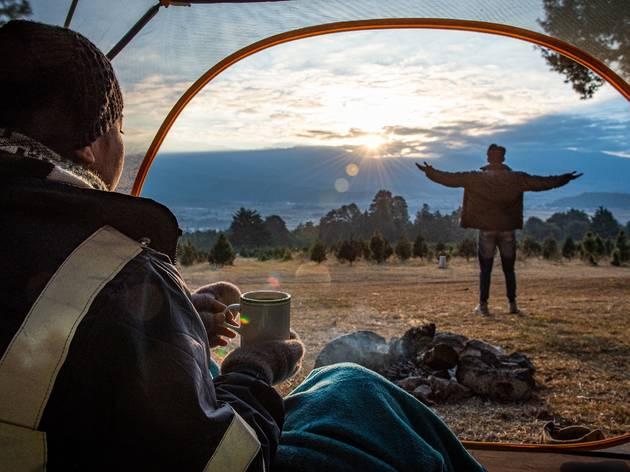 Mujer bebe taza de café dentro de casa de acampar
