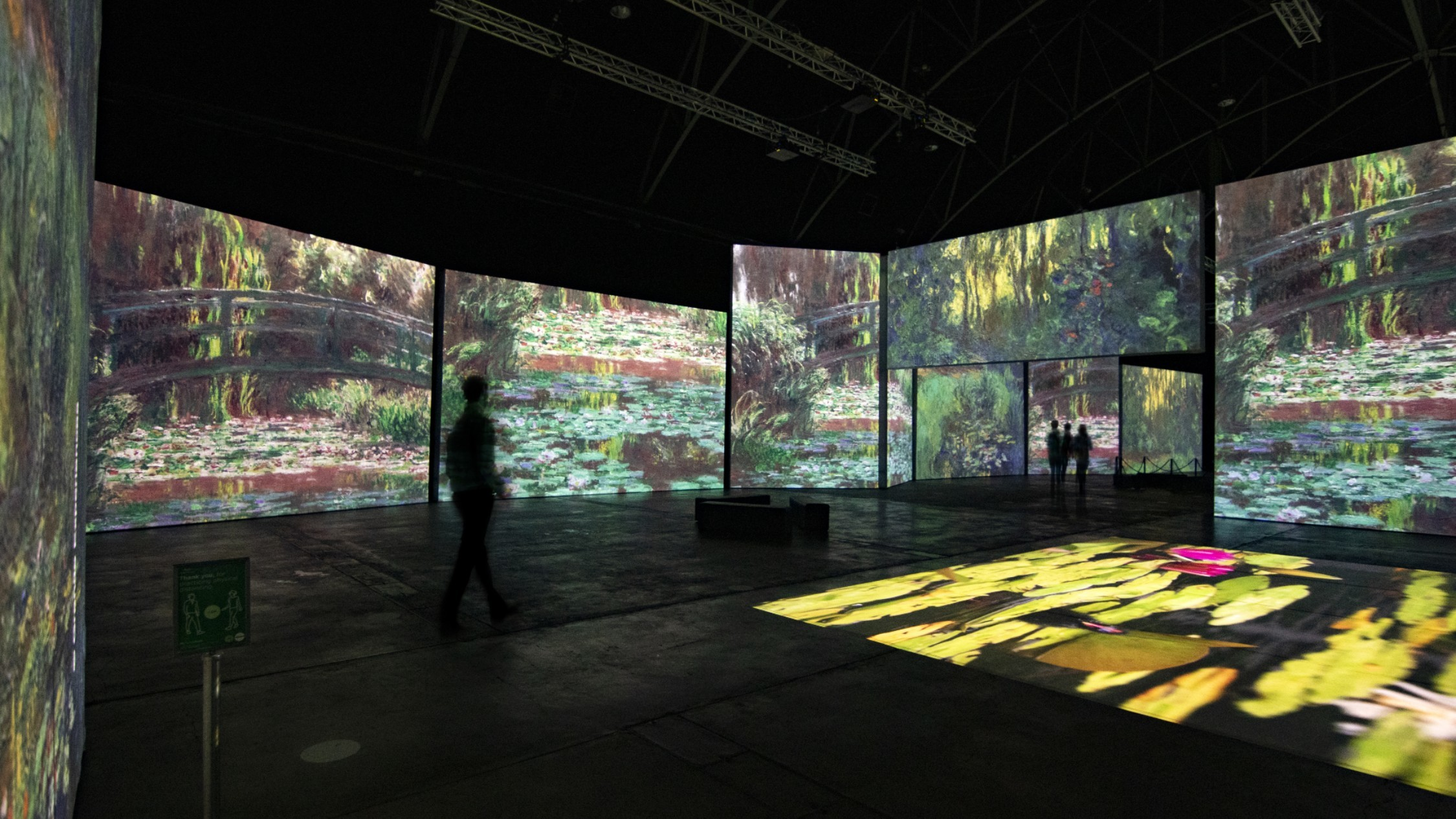 A silhouetted figure in front if IMAX-sized projections of Monet's famous water lily paintings