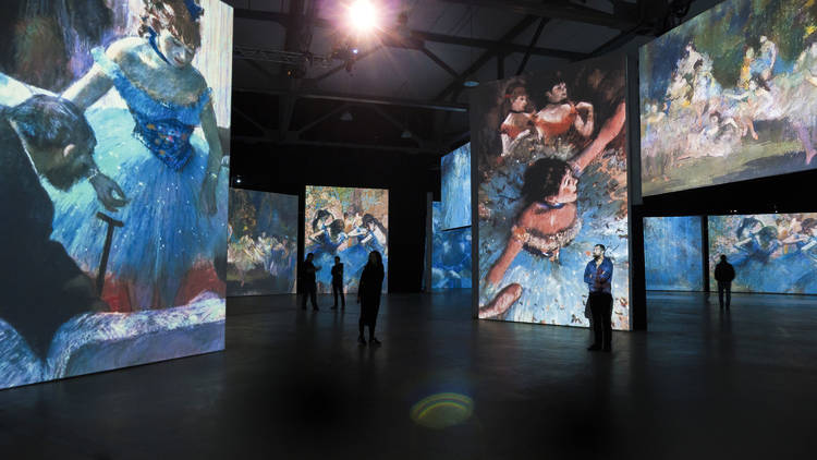 Silhouetted figures in front if IMAX-sized projections of Degas' famous dancer paintings