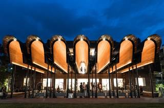 An exterior shot of the Joynton Avenue Creative Centre at dusk, with it's wooden arches aglow