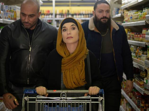 Isabell Huppert wearing a hijab and flanked by heavies in a supermarket