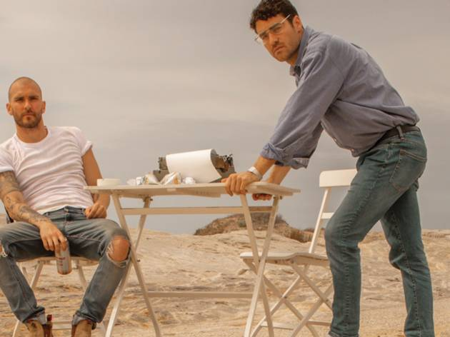 Two brothers in denim sitting at a table in the desert