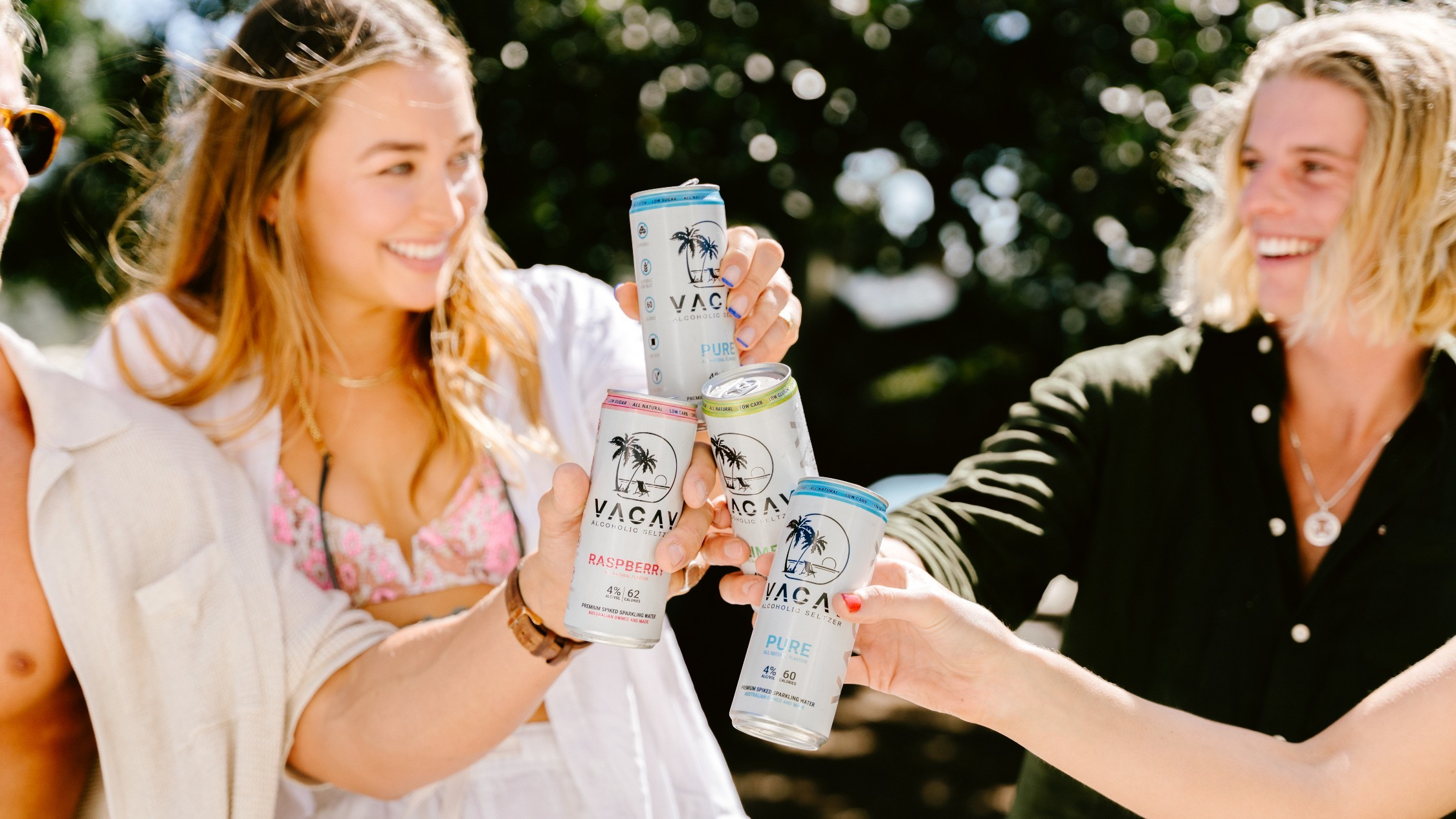 A group of people cheers together cans of hard seltzer in the sunshine.