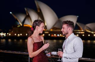 Man and woman drink Champagne on deck of boat, Sydney Opera House is behind them