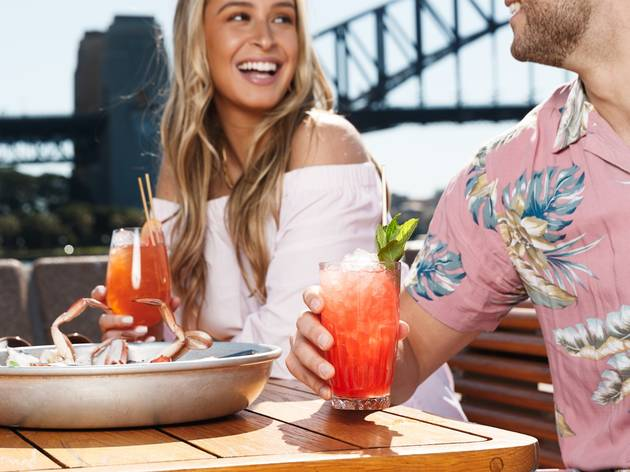 A couple enjoys a tequila cocktail at Opera bar with the Harbour Bridge in the background