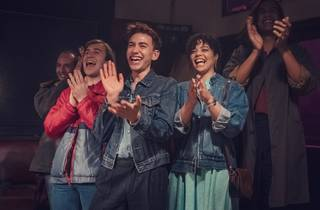 The cast of Stan show It's a Sin applauding in '80s attire