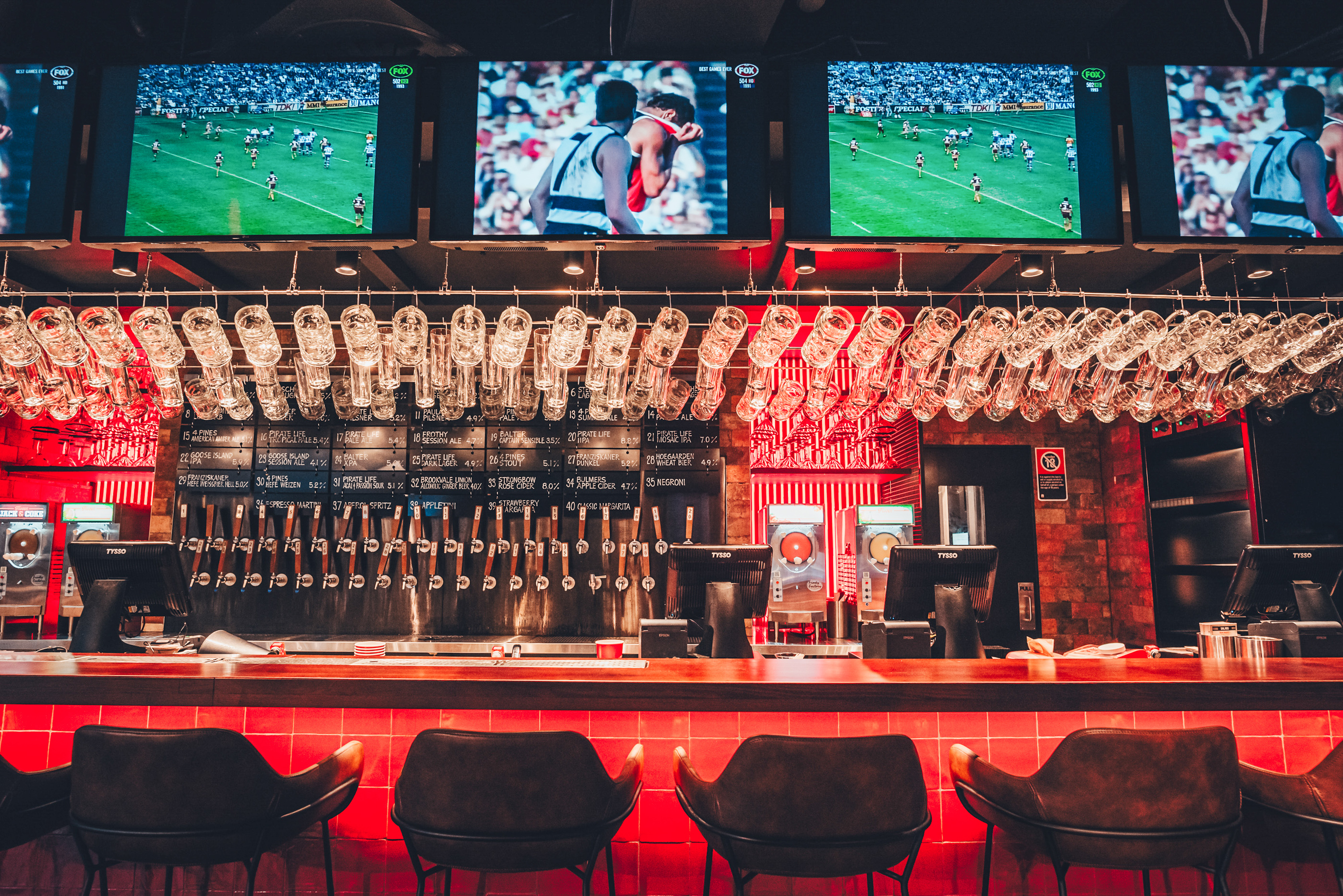 A red-lit bar iwth glasses hanging overhead and sports on multiple screens
