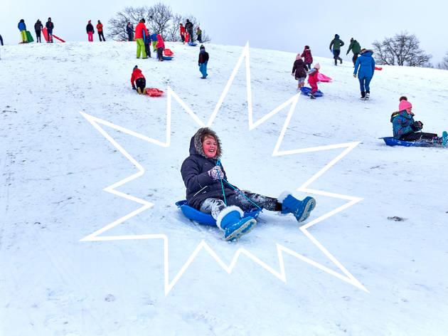 children sledging on a snowy field
