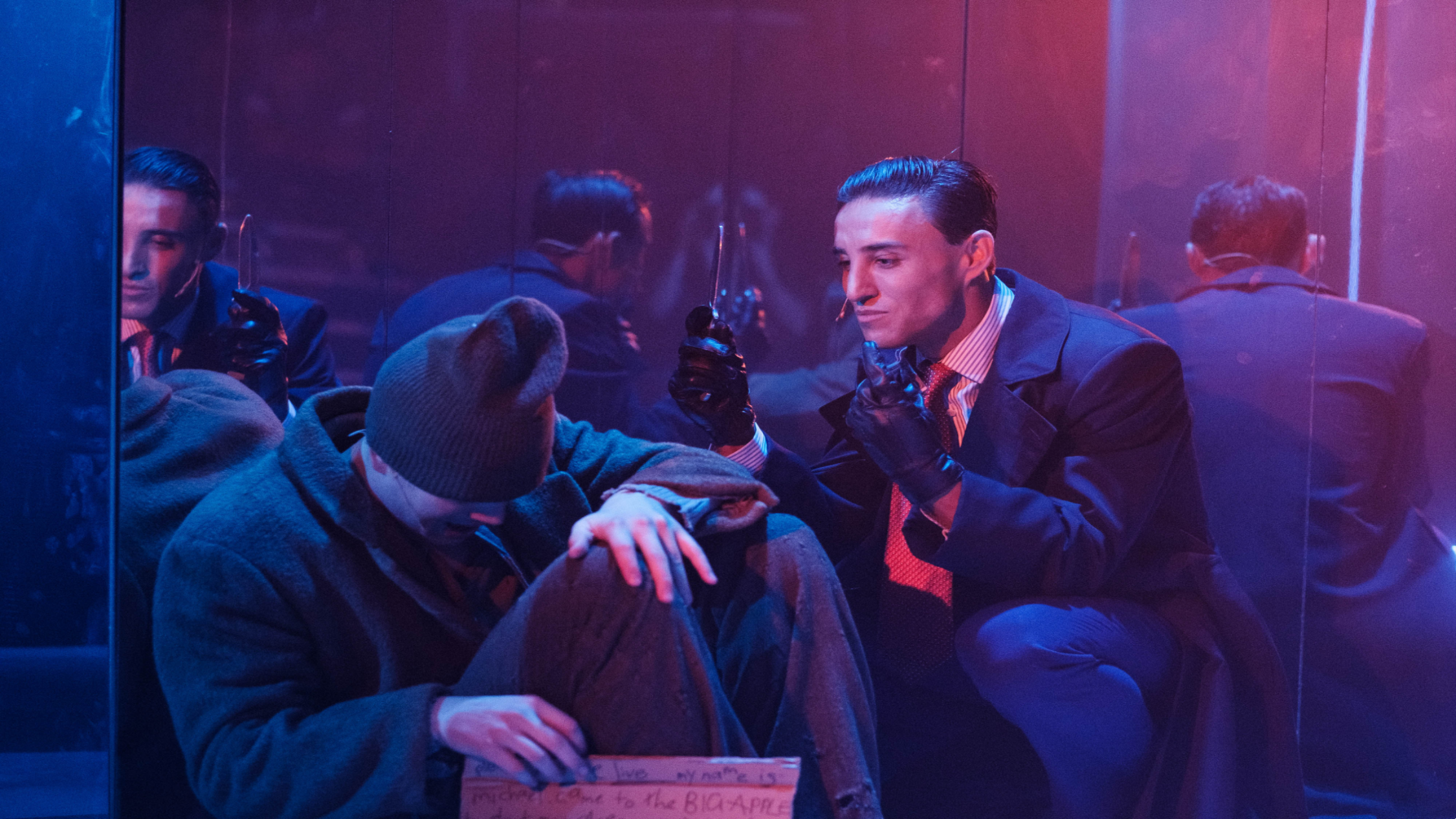 A suited Ben Gerrard in leather gloves menaces a homeless man with a knife in American Psychopath the Musical