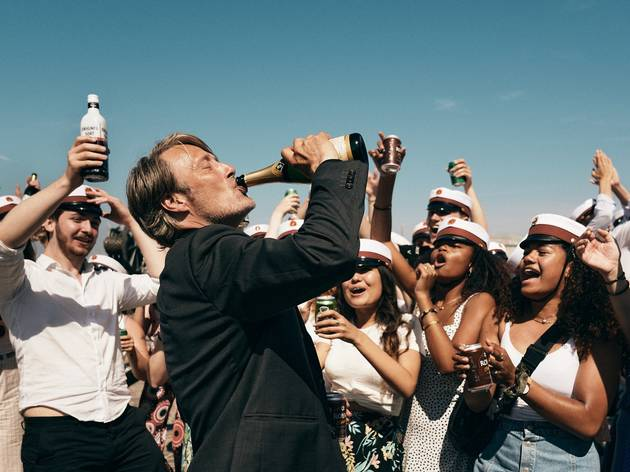 Mads Mikkelsen drinking a beer in front of high school graduates in sailor hats