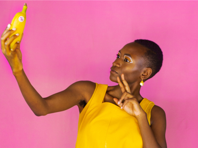 Moreblessing Maturure in a yellow dress holding a banana against a pink backdrop
