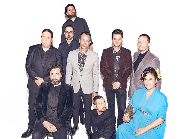 The nine members of The Bamboos stand around in front of a white background. Seven members are in dark suits and the vocalist is seated wearing an azure blue dress holding a fan.