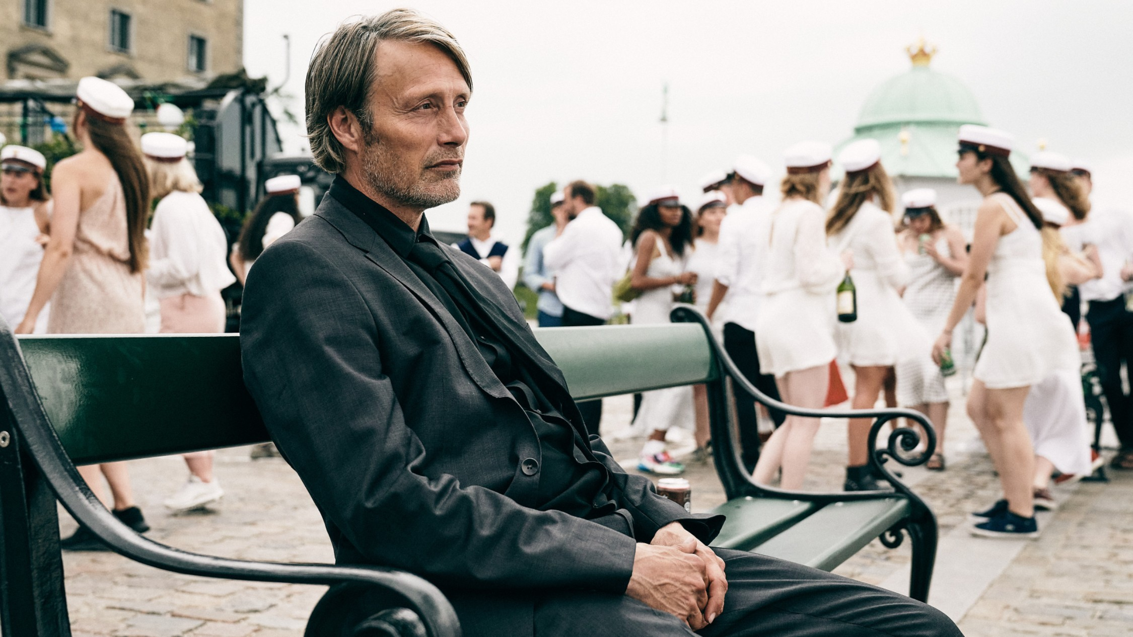 Mads MIkkeslen in a dark suit sits on a bench with students in sailor outfits in the background