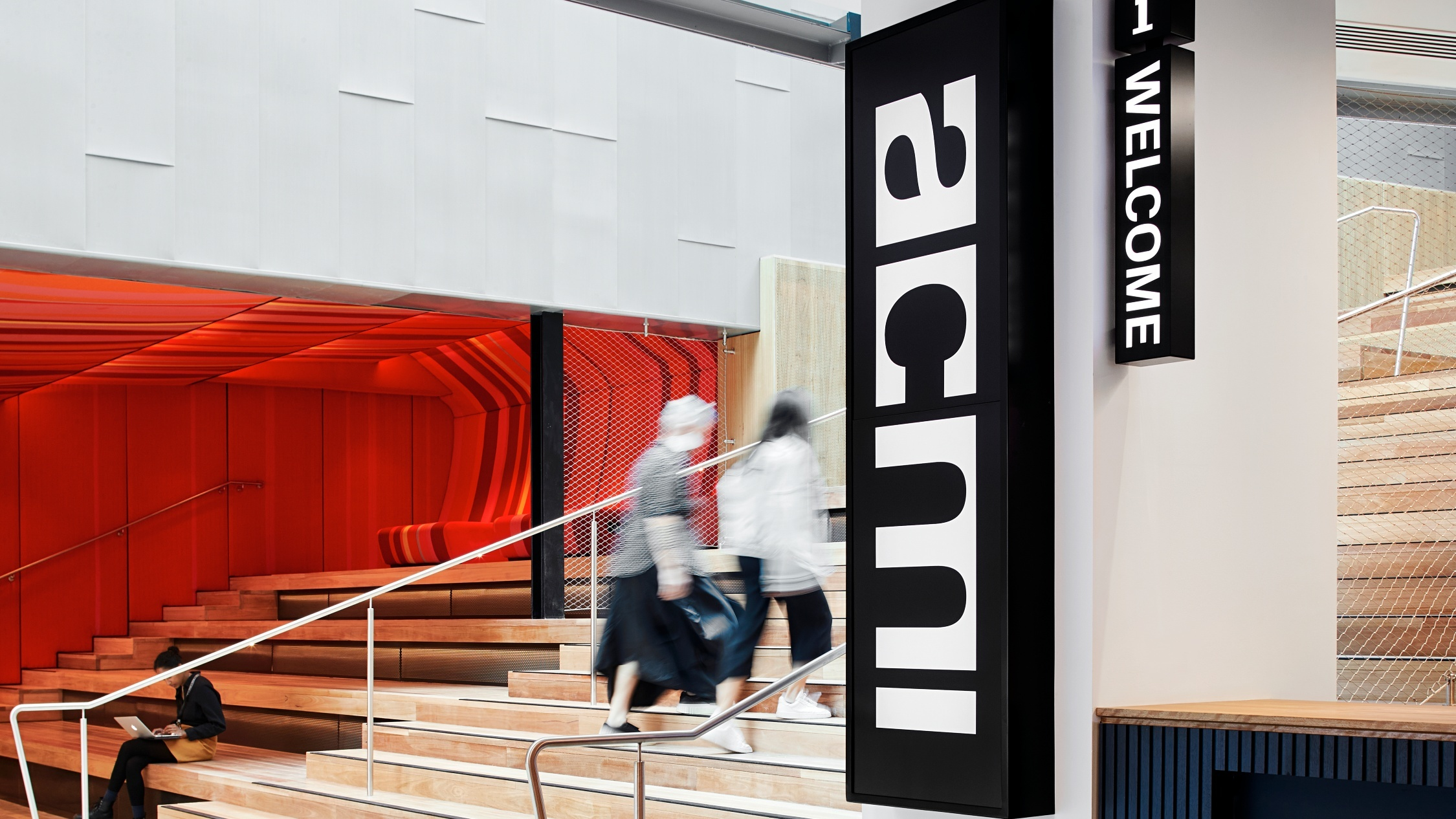 Two people on the ACMI staircase, with an ACMI sign in the foreground