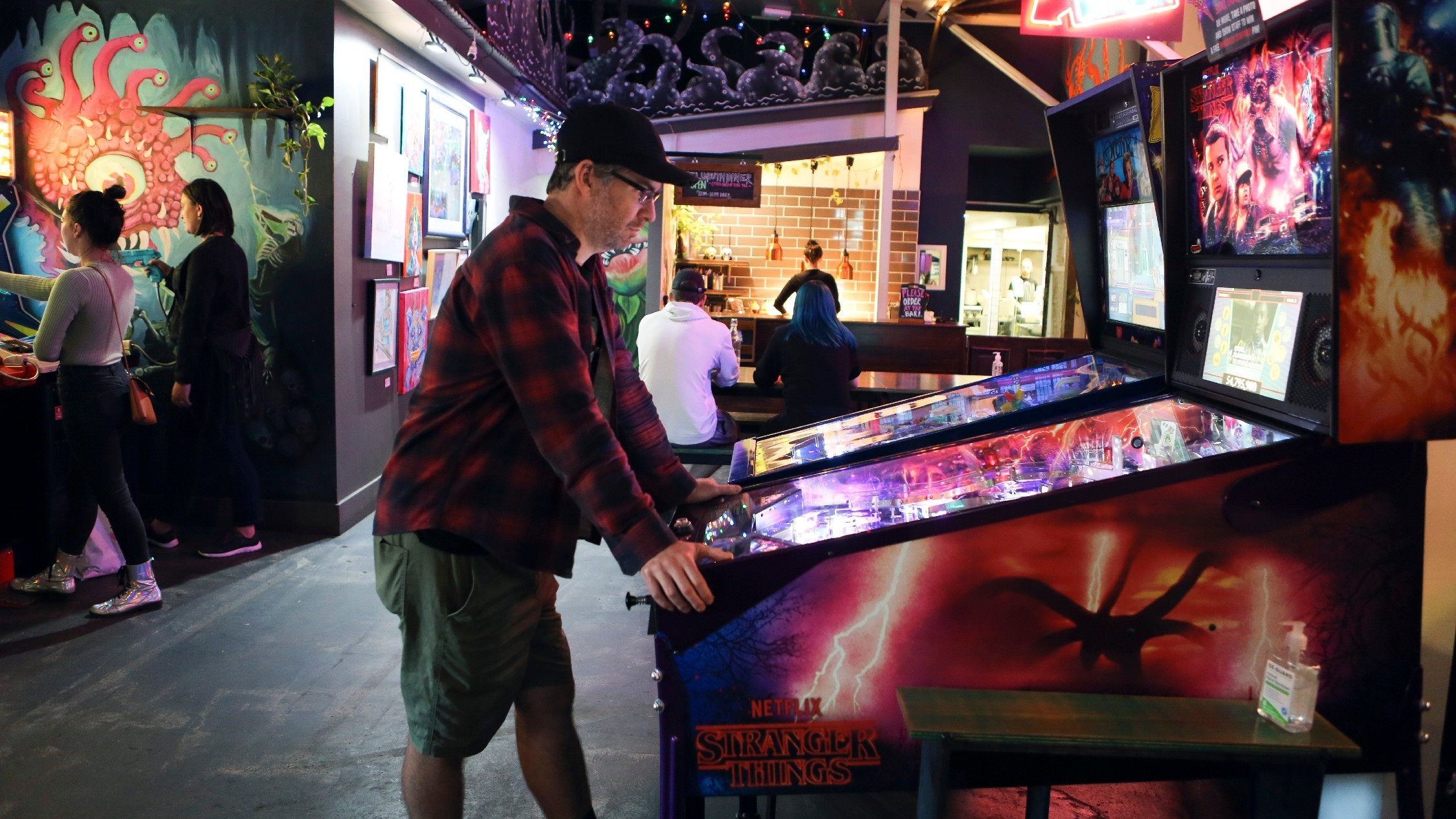 Man in cap playing pinball at Netherworld Arcade