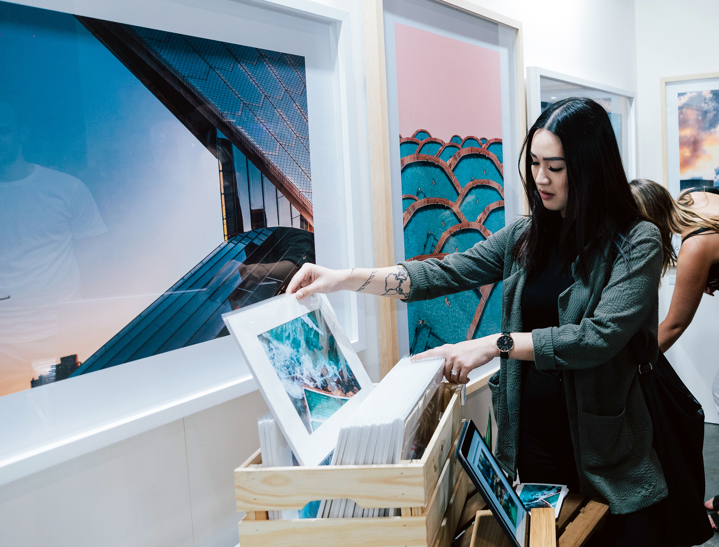 A person lifts a photo print from a crate full of prints. There are large framed artworks surrounding them. They are wearing a cool black outfit.