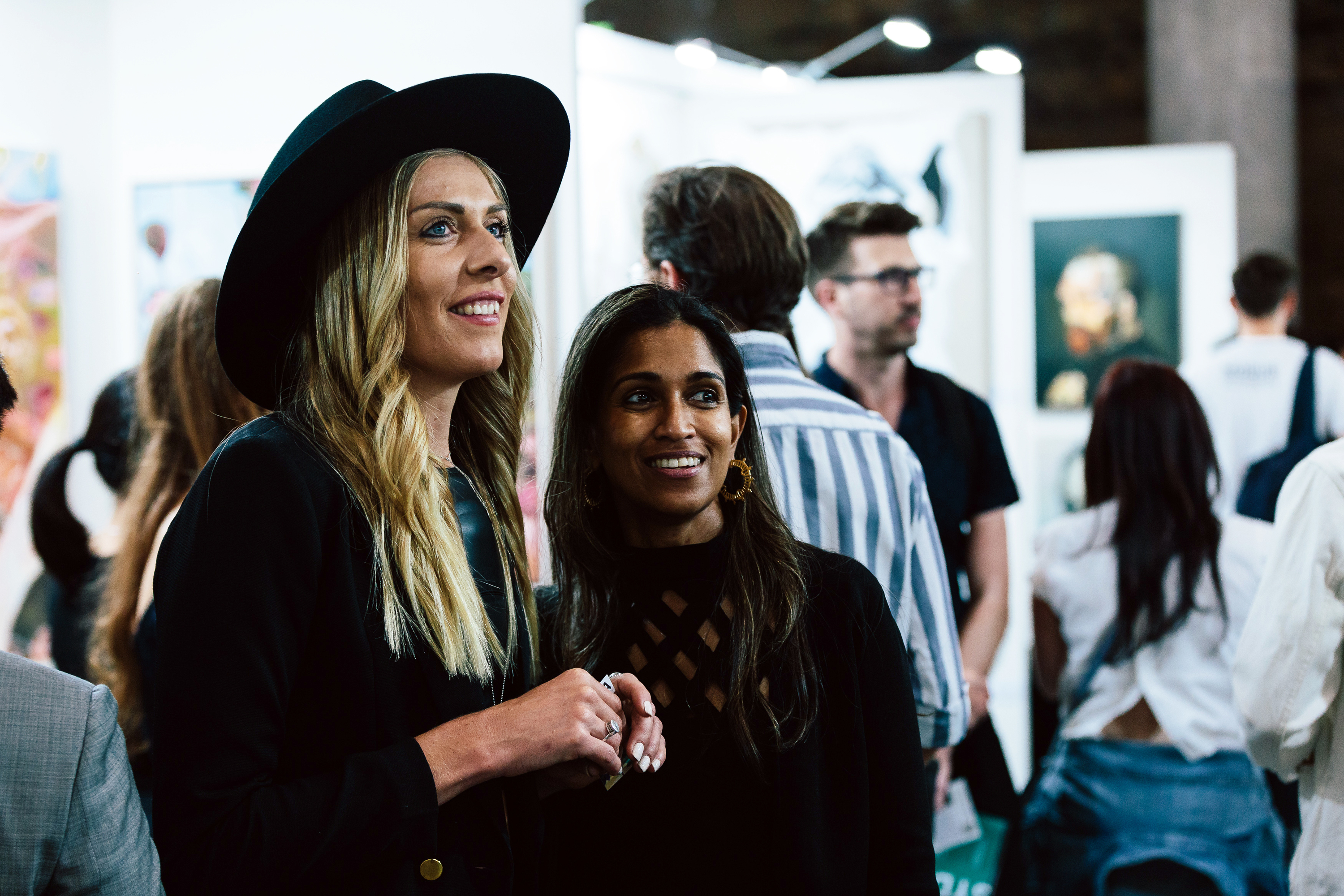 Two people in elaborate black outfits smile into the middle distance. They are looking at an artwork out of frame. There is a crowd browsing art on partition walls in the background.