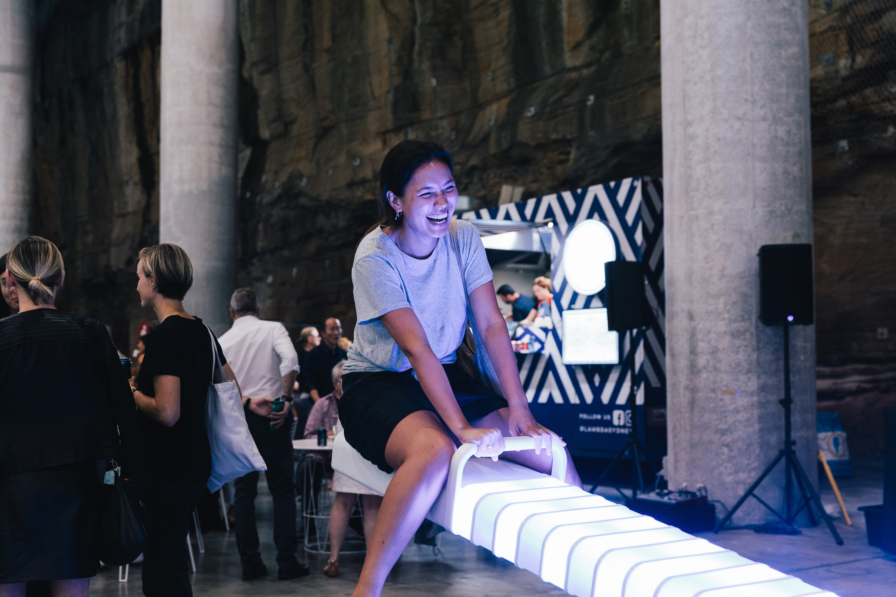 A person smiles atop a glowing see-saw at the Cutaway in Barangaroo.