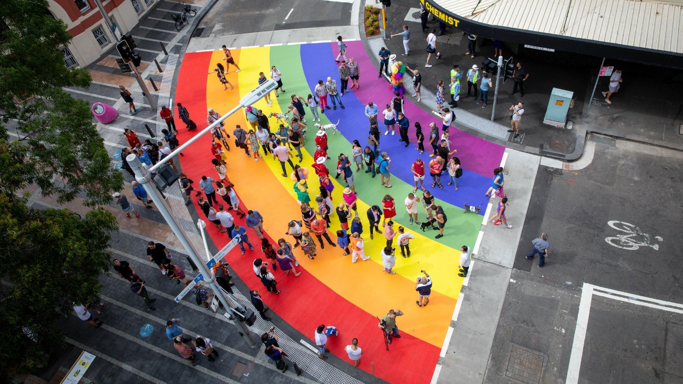 Crowd crosses road at rainbow crossing.