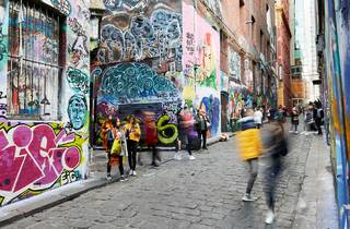 People walking through Hosier Lane which features bluestone pavers and street art all over the laneway