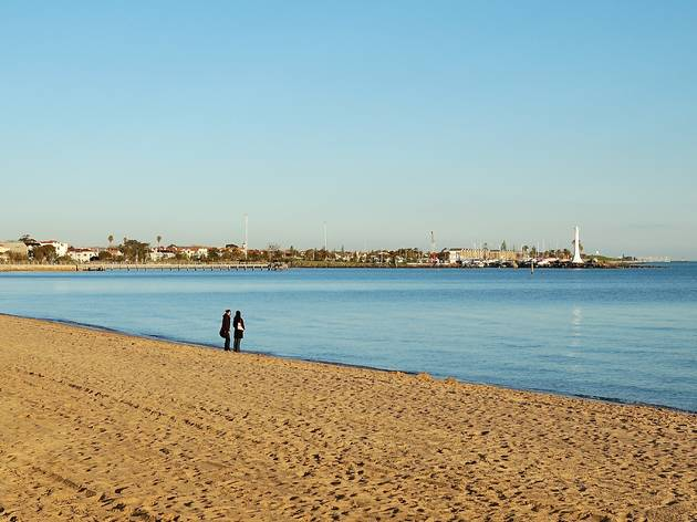 Two people standing in the distance on St Kilda beach at Sunset