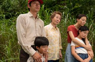 The Korean American family of film Minari huddle in front of green shoots