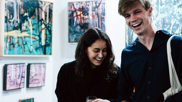 Two people laugh in a booth filled with paintings at the Other Art fair.