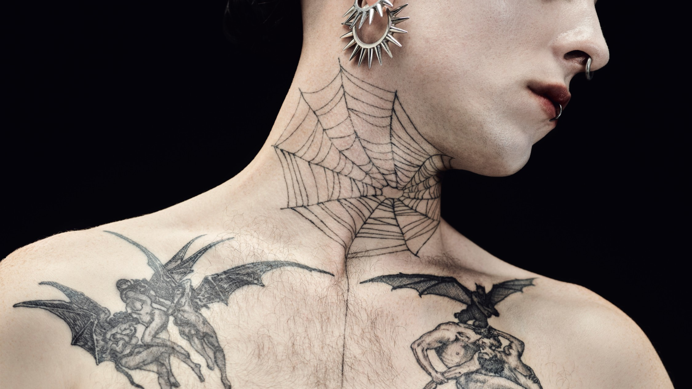 A close up of a pale man's lower face and upper torso with spider web tattoo