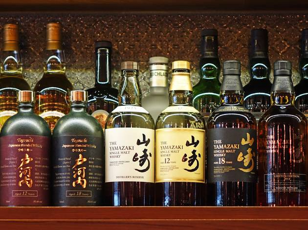Six Japanese whisky bottles on a bar shelf in front of more bottles