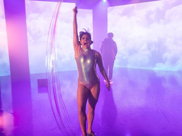 A woman in a sparkly leotard waves ribbon enthusiastically through the air