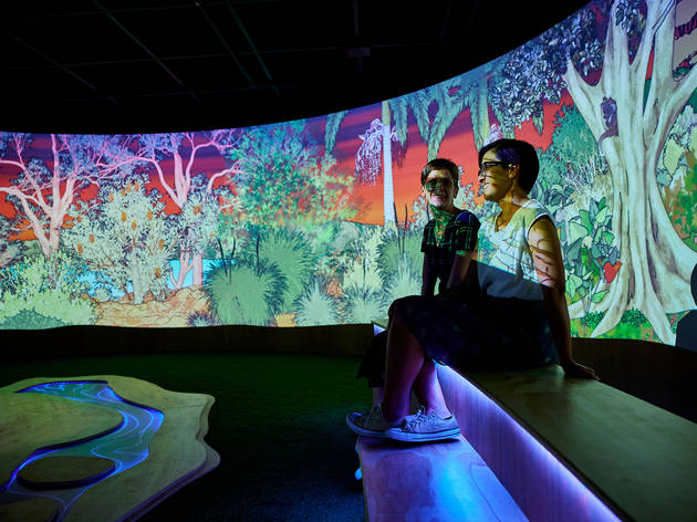 Two people sit in a video projection installation.