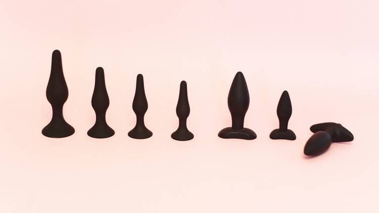 Row of different size and shaped small black sex toys on pink backdrop.