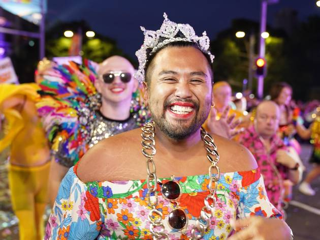 Person standing in the Mardi Gras Parade, they are smiling and wearing a crown.