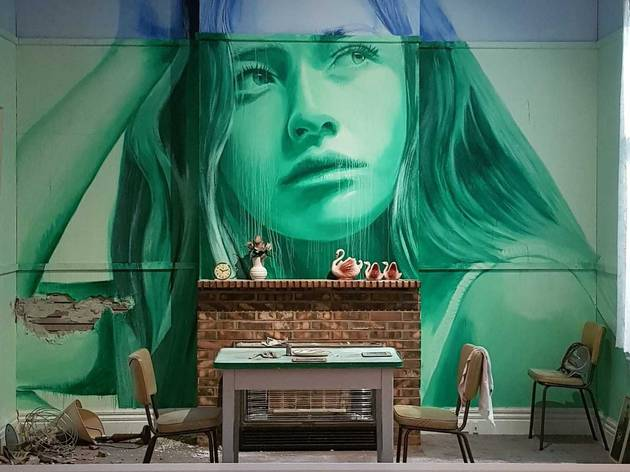 An installation featuring a room in disrepair. There is a table and two chairs plus a brick fireplace; on the wall behind the fireplace is  mural of a woman painted in green and blue