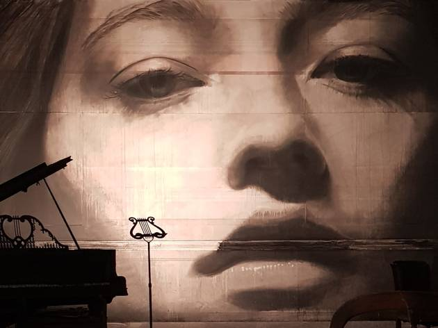 A dark mural of a woman's face; a baby grand piano is backlit in the foreground