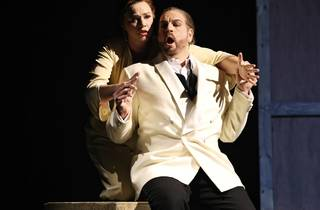A man in a white tuxedo jacket duets with a woman holding him from behind