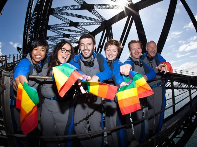 A group of people wave rainbow flags from a Harbour Bridge climb.
